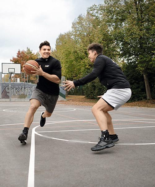 Zwei Sportler spielen gemeinsam Basketball und tragen sportomedix Produkte
